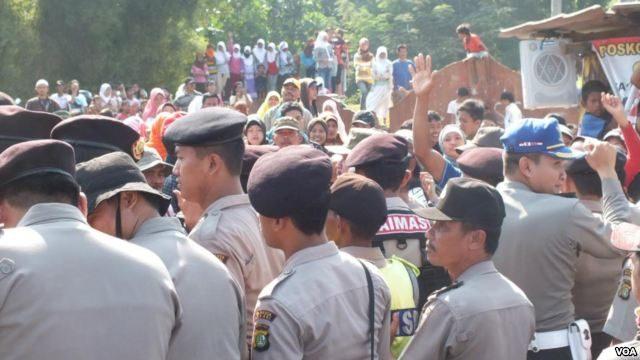 Polisi menjaga jemaat Gereja HKBP Filadelfia di Bekasi saat dihadang kelompok massa yang melarang mereka beribadah, 2012. (Foto: Dok))
