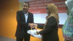 Presiden Direktur PT Novartis Indonesia, dr.Luthfi Mardiansyah memberikan donasi kepada salah satu perawat dari Yayasan Rumah Rachel , Susi Susilawati di Axa Tower, Setiabudi Kuningan pada Selasa, (16/7) (sumber: Beritasatu.com)