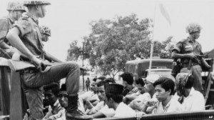 Anggota divisi pemuda Partai Komunis Indonesia (PKI) dijaga oleh tentara saat dibawa dengan truk ke penjara di Jakarta, 30 Oktober 1965. (Foto: Dok)