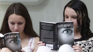 Olivia Jackson, 15 tahun, kiri, dan Julia Cebula, 14 tahun, dari Philadelphia, membaca buku terbaru dari EL James, 'Grey,' saat mengantri untuk mendapatkan tanda tangan penulis tersebut di toko buku Barnes and Noble di New York.